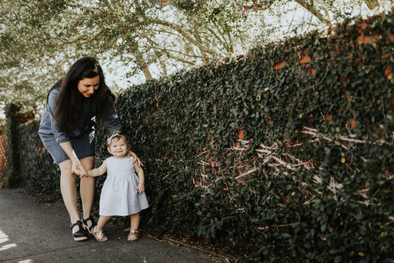 mother and daughter walking by ivy covered wall