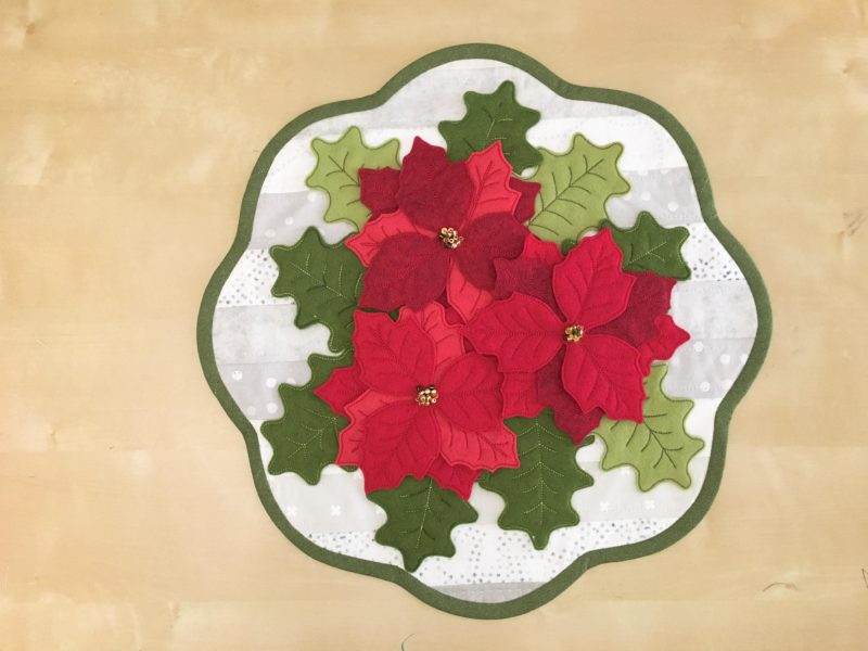 felt poinsettia and holly leaves on qhite background