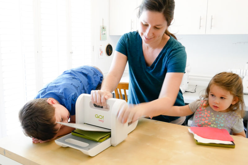mom and kids using fabric cutter