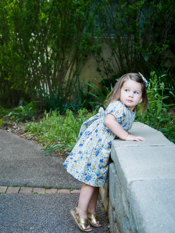 baby girl leaning over bridge