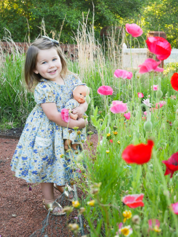 girl holding baby doll in flower garden