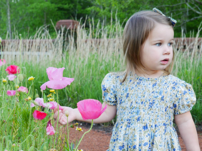 toddler wearing floral dress standing in garden