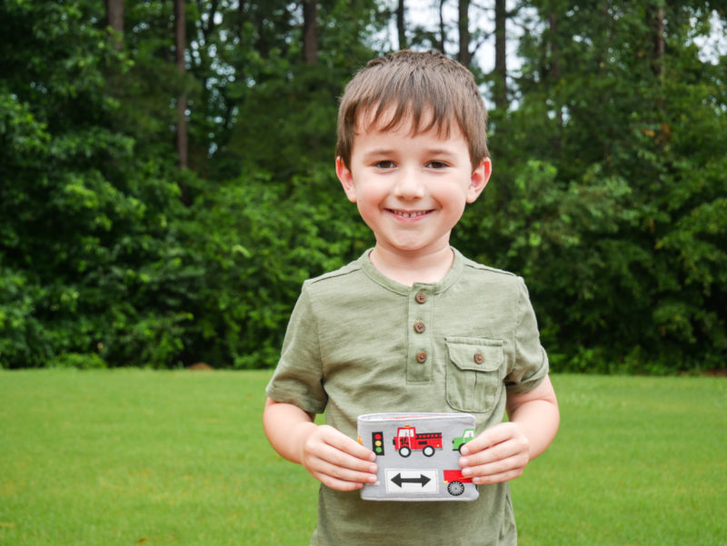 boy holding closed wallet he made with trucks