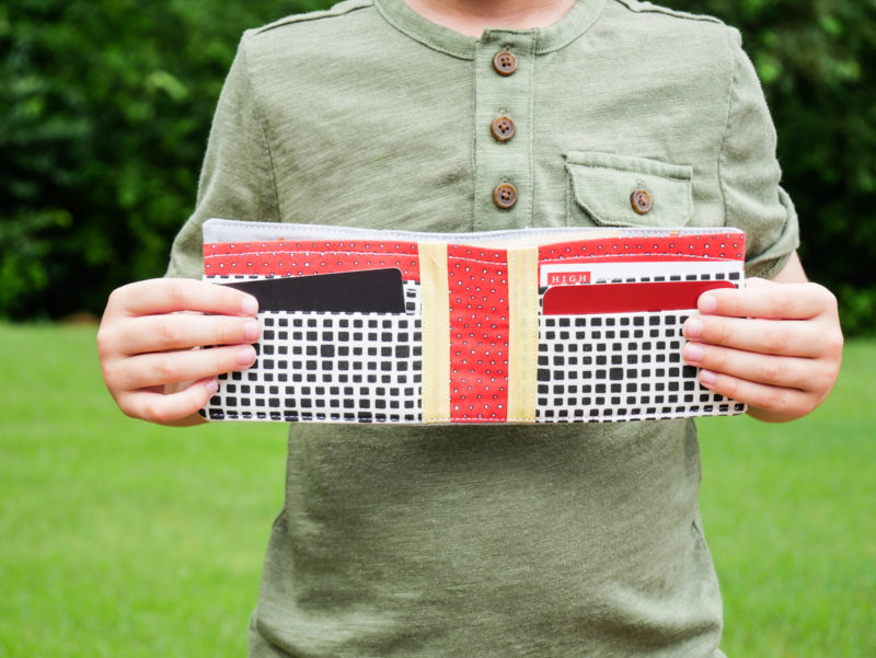 boy holding open wallet he made with trucks